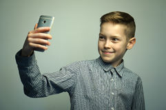 Nastoletnia poważna chłopiec z eleganckim ostrzyżeniem bierze selfie na smartphone Obrazy Stock