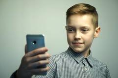Nastoletnia poważna chłopiec z eleganckim ostrzyżeniem bierze selfie na smartphone Obrazy Royalty Free