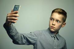 Nastoletnia poważna chłopiec z eleganckim ostrzyżeniem bierze selfie na smartphone Zdjęcie Stock