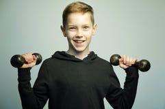 Nastoletnia sport chłopiec z dumbbells i eleganckim ostrzyżeniem, studio strzał Fotografia Stock
