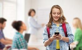 Nastoletnia studencka dziewczyna z szkoln? torb? i smartphone fotografia royalty free