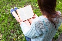 Nastoletnia szczęśliwa dziewczyna czyta książkę w miasto parku plenerowym obraz royalty free