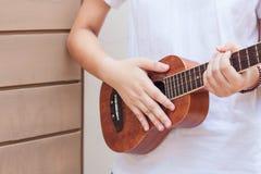 Nastoletnie azjatykcie kobiety z ukulele w jej czasie wolnym Fotografia Stock