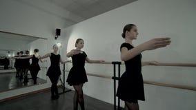 Nastoletnie baleriny ubierać w czarnych leotards odzwierciedlać korytarz są tanem blisko baletniczego barre i tamte odbicie zdjęcie wideo
