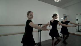 Nastoletnie baleriny ubierać w czarnych leotards są tanem blisko baletniczego barre Balet klasy Gładcy baletniczy podstawy ruchy zbiory wideo