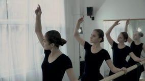 Nastoletnie baleriny ubierać w czarnych leotards są tanem i okno blisko baletniczego barre Baleriny robią gładkim rękom zbiory