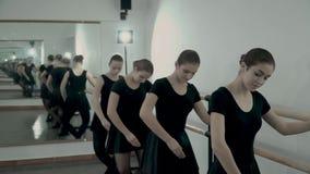 Nastoletnie baleriny ubierać w czarnych leotards są tanem Plie i PLIE RELEVE blisko baletniczego barre i tamte odbicie zbiory wideo
