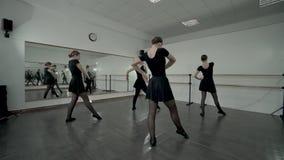 Nastoletnie baleriny ubierali w czarnych leotards robią baletniczego ruchu całkowicie podczas gdy nauczycieli spojrzenia przy one zbiory wideo