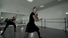 Nastoletnie baleriny ubierali w czarnych leotards robią baletniczego ruchu całkowicie podczas gdy nauczycieli spojrzenia przy one zdjęcie wideo