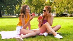 Nastoletnie dziewczyny je arbuza przy pinkinem w parku zbiory