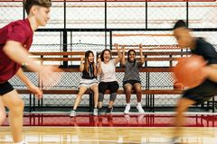Nastoletnie dziewczyny rozwesela chłopiec bawić się koszykówkę zdjęcie royalty free