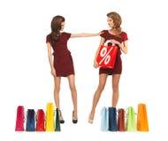 Nastoletnie dziewczyny w czerwonych sukniach z torba na zakupy Obrazy Royalty Free