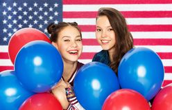 Nastoletnie dziewczyny z balonami nad flagą amerykańską zdjęcie stock