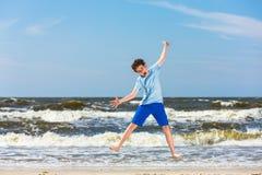 Nastoletniego chłopaka doskakiwanie, biega na plaży Zdjęcia Royalty Free