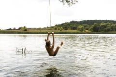 Nastoletniego chłopaka doskakiwanie w rzece od kołyszącej arkany na pogodnym letnim dniu zdjęcia stock