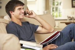 Nastoletniego Chłopaka obsiadanie Na kanapie Robi pracie domowej W Domu Używać telefon komórkowego obraz stock