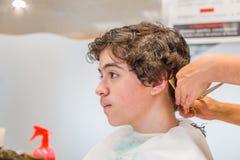 Nastoletniego chłopaka obsiadanie przy fryzjera salonem dla ostrzyżenia fotografia stock