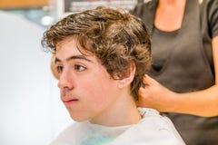 Nastoletniego chłopaka obsiadanie przy fryzjera salonem dla ostrzyżenia obraz royalty free