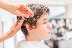 Nastoletniego chłopaka obsiadanie przy fryzjera salonem dla ostrzyżenia obraz stock