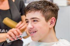 Nastoletniego chłopaka obsiadanie przy fryzjera salonem dla ostrzyżenia fotografia royalty free