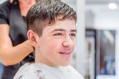 Nastoletniego chłopaka obsiadanie przy fryzjera salonem dla ostrzyżenia zdjęcie royalty free