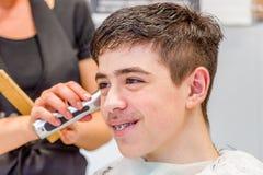 Nastoletniego chłopaka obsiadanie przy fryzjera salonem dla ostrzyżenia obrazy royalty free