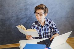 Nastoletniej chłopiec czytelnicza książka i use laptop w domu Zdjęcia Royalty Free