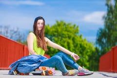 Nastoletniej dziewczyny łyżwiarki jazdy deskorolka na ulicie Zdjęcie Stock