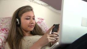 Nastoletniej Dziewczyny lying on the beach Na Łóżkowym Używa laptopie Podczas gdy Texting zbiory