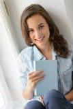 Nastoletniej dziewczyny obsiadanie nadokienną chwyt książką Zdjęcia Royalty Free