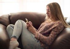 Nastoletniej dziewczyny obsiadanie w krześle i cieszy się smartphone Zdjęcia Royalty Free