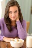 Nastoletniej dziewczyny obsiadanie za stołowym zboża śniadaniem Fotografia Stock