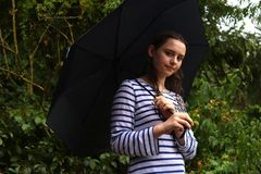 Nastoletniej dziewczyny pozycja pod parasolem w deszczu zdjęcie stock