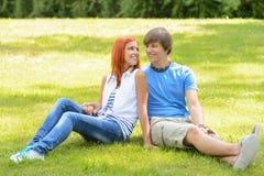Nastoletniej pary siedząca trawa patrzeje each inny Zdjęcie Royalty Free