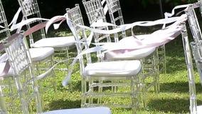 Nastri bianchi e rosa che fluttuano sulle sedie La cerimonia di nozze Sedie trasparenti stock footage
