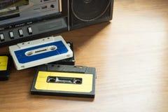 Nastri a cassetta d'annata con il giocatore della radio-cassetta sull'tum di legno Fotografia Stock