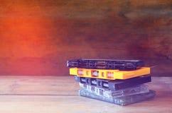 Nastri a cassetta della pila sopra la tavola di legno retro filtro Fotografie Stock Libere da Diritti