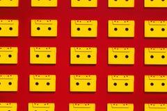 Nastri a cassetta gialli della raccolta audio su fondo rosso, vista superiore Concetto creativo di retro tecnologia Fotografie Stock Libere da Diritti