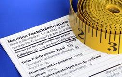 Nastri di misurazione sui fatti di nutrizione Fotografia Stock Libera da Diritti