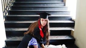 Nastri matrici laureati del bello studente la sua gamba con un gesso mentre sedendosi sui punti del metallo all'università stock footage