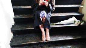 Nastri matrici laureati del bello studente la sua gamba con un gesso mentre sedendosi sui punti del metallo all'università video d archivio