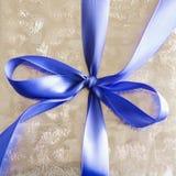Nastro blu legato in un arco sul regalo d'argento. Fotografie Stock
