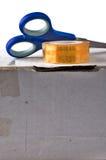 Nastro con le forbici sulla scatola di cartone Immagini Stock Libere da Diritti