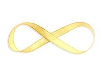 Nastro del raso dell'oro con forma di infinito Immagine Stock