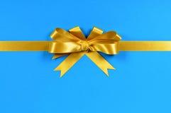 Nastro dell'arco del regalo dell'oro sull'orizzontale blu del fondo Fotografia Stock