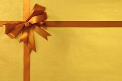 Nastro dell'arco del regalo di compleanno o di Natale, stagnola metallica dell'oro del fondo, spazio della copia Fotografia Stock