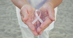 Nastro di consapevolezza del cancro al seno in mani della donna archivi video