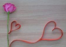 Nastro di forma del cuore di due rossi con la rosa di rosa su superficie di legno con spazio per testo fotografia stock