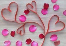 Nastro di forma del cuore di quattro rossi con il rosa ed i petali di rosa rossa su superficie di legno fotografia stock libera da diritti