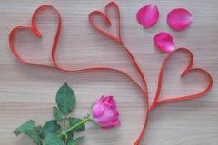 Nastro di forma del cuore di tre rossi con i petali rosa rosa su superficie di legno immagini stock
